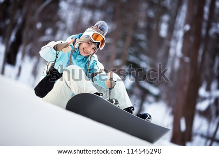Young female snowboarder sitting on slope and showing thumbs up