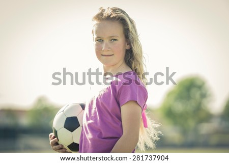 Young female soccer player posing with ball - stock photo