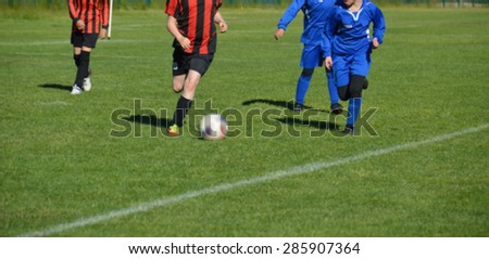 Young female soccer players running on grass field. European football girl team. Young women playing soccer. Female players in tournament. Blurred image.