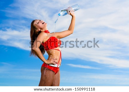 Young female sport girl in red uniform with a bottle of water