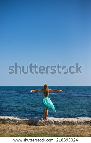 young female standing at the port, near by the blue sea with back,freedom