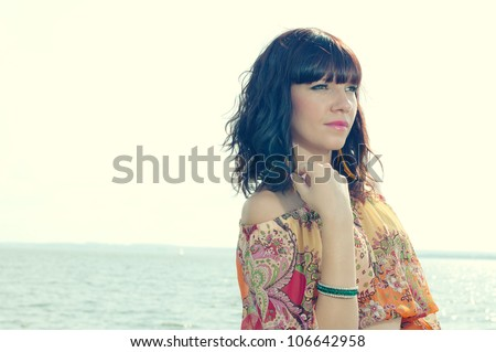 Young female standing near the shore and looking at sea waves - stock photo