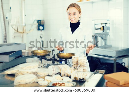 Young female standing with box of turron in production workshop