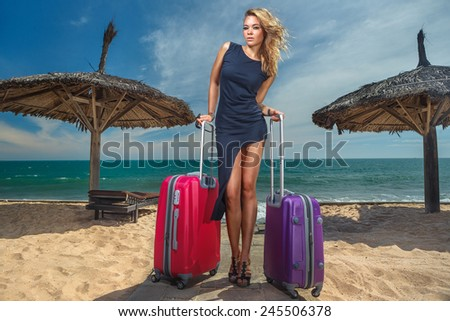 Young female stay with a suitcases on the beach - stock photo