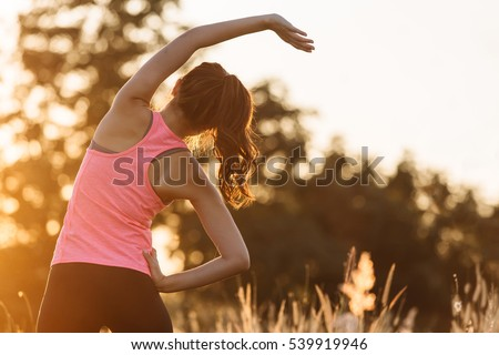 Young female  stretching before fitness training session at the park. Healthy young woman warming up outdoors. She is stretching her arms and looking away,hi key.