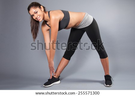young female stretching in the studio  - stock photo