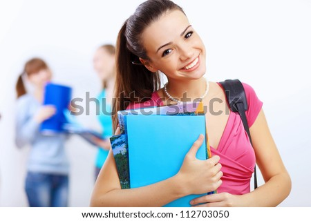 Young female student at college with books - stock photo