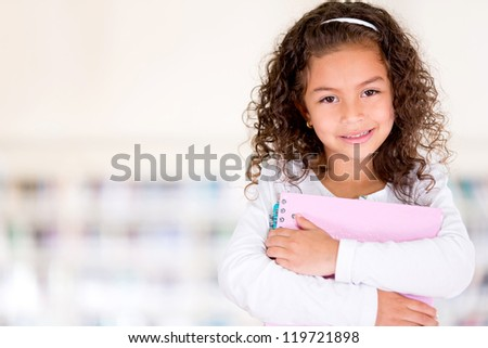 Young female student at school holding notebooks - stock photo