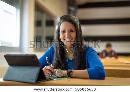 Young female student at university classroom.  She's using tablet and headphones for taking notes to study.