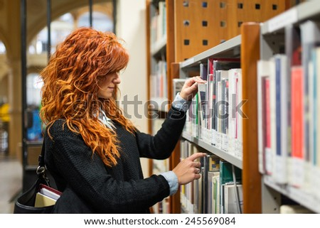 Young female student consulting book from shelf in public library.