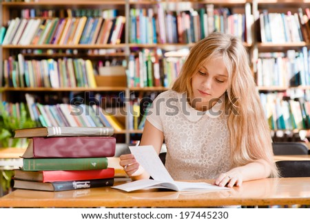 young female student doing assignments in library - stock photo