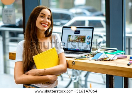Young female student holding yellow book with laptop and colorful stuff on the table near the window with street view in the cafe or studio - stock photo