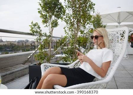 Young female student is enjoying rest and good day, while sitting with smart phone in cozy cafe terrace. Beautiful woman tourist is using cell telephone and relaxing after walking in a strange city - stock photo