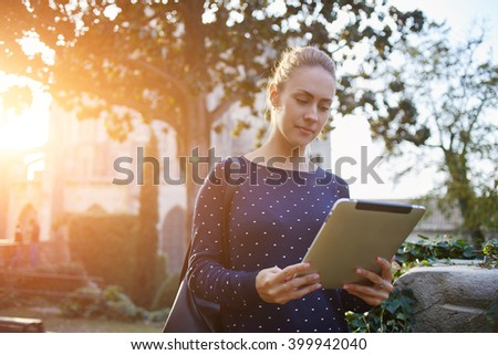 Young female student is using touch pad for preparing to exam in university,while is standing on campus. Woman tourist is searching on digital tablet information about history city during walking tour - stock photo