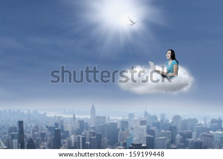 Young female student looking at dove and using a laptop sitting on clouds