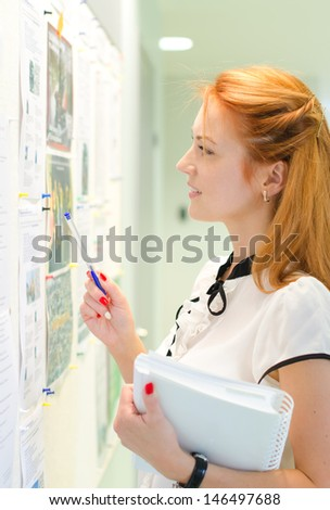 Young female student looking through job offers on board - stock photo