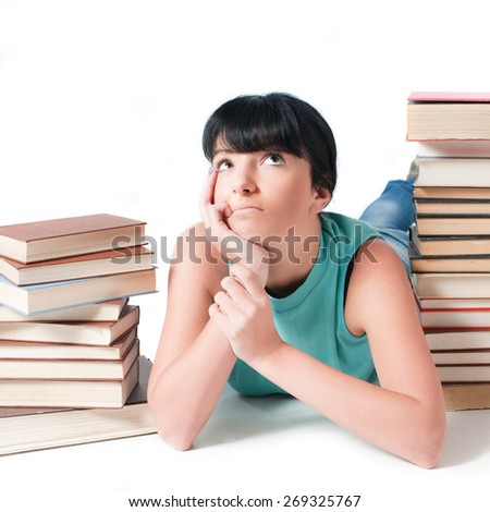 Young female student lying between her books