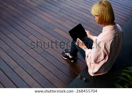 Young female student sitting in a university recreation hall using touch pad,freelancer girl working on her digital tablet with big copy space, hipster woman using touchscreen device in modern office - stock photo