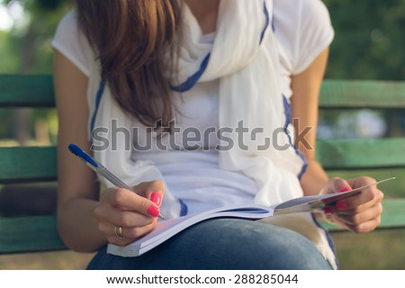 Young female student sitting on a bench in the park. She takes notes in a notebook. She is dressed in blue jeans and white T-shirt. Close-up. - stock photo