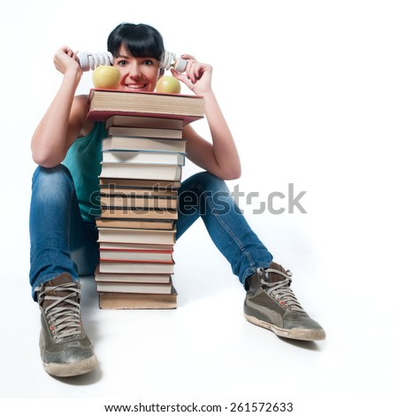 Young female student sitting with books, energy saving light bulbs and apples