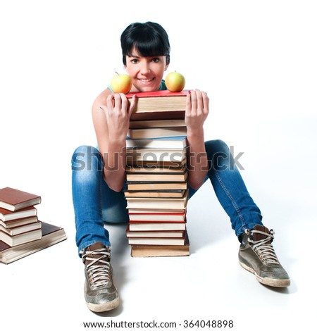 Young female student sitting with her books and apple on its