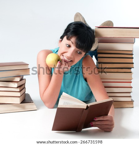 Young female student with apple lying and reading a book