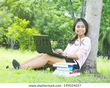 Young female student with laptop sit relaxed green grass