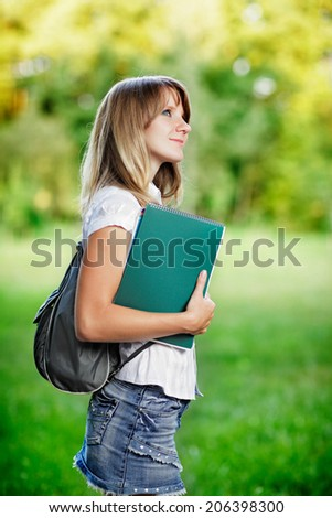 Young female student with workbook standing on green blurred grass background