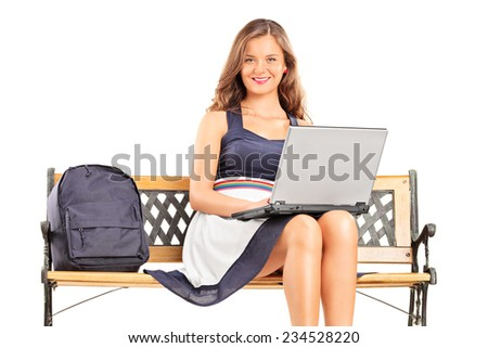 Young female student working on a laptop seated on a bench isolated on white background - stock photo