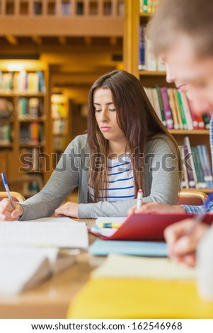 Young female student writing notes at desk in the college library
