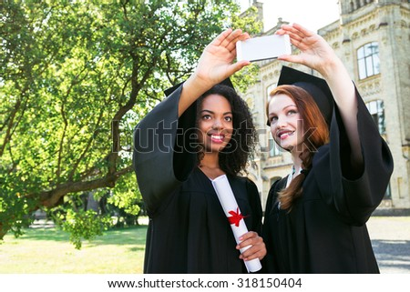 Young female students dressed in black graduation gown. Campus as a background. Girls smiling and making selfie photo on mobile phone - stock photo