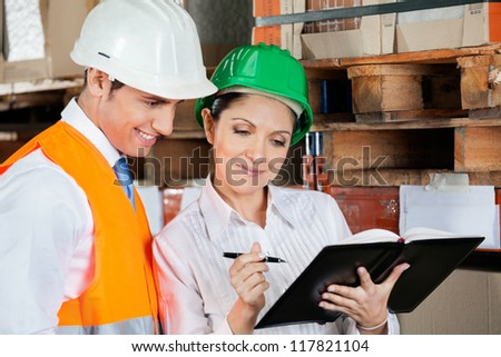 Young female supervisor and colleague working at warehouse - stock photo