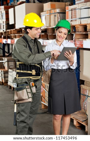 Young female supervisor and foreman using digital tablet at warehouse