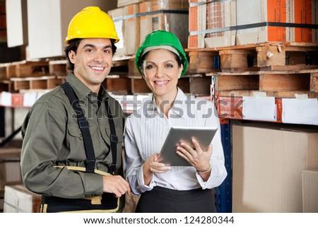 Young female supervisor instructing foreman at warehouse - stock photo