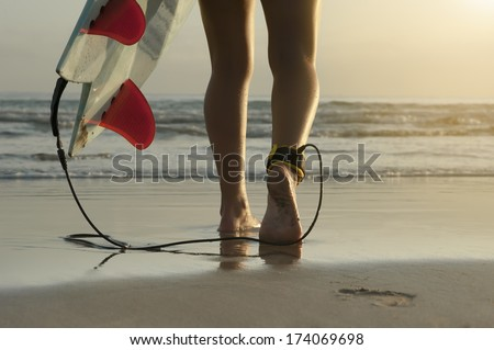 Young female surfer girl feet surfboard early morning surf  - stock photo