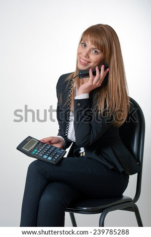 Young female talking by the phone and holding a calculator in her hand - stock photo