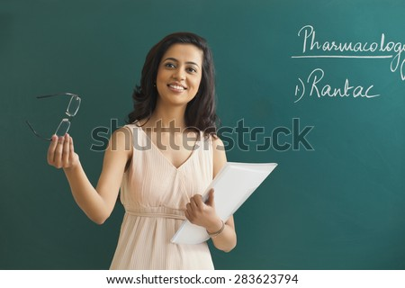 Young female teacher looking away while holding glasses and file against green board - stock photo