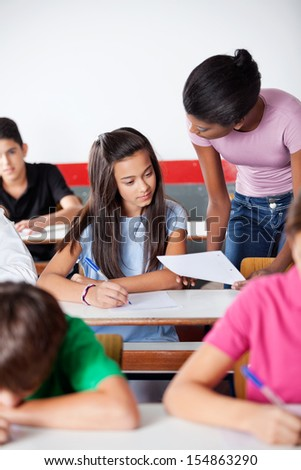 Young female teacher showing paper to female student at desk with classmates in classroom - stock photo