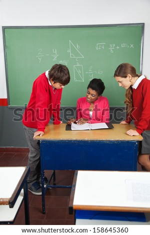 Young female teacher teaching teenage students at desk in classroom - stock photo