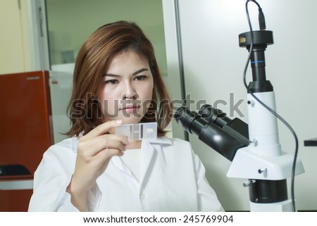 Young female tech or Scientist using a microscope and check result of sample on glass in a laboratory - stock photo