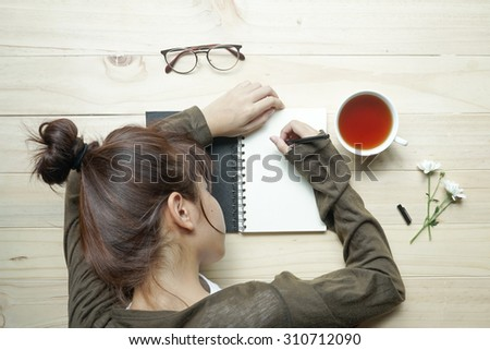 young female teenager writing or drawing on notebook with cup of tea and white flowers on wooden table. Top view - stock photo