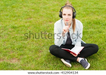 Young female thinking and writing while listening music outdoors on heandphones with copy space - stock photo