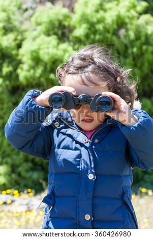Young female toddler looking through a pair of binoculars towards the camera.