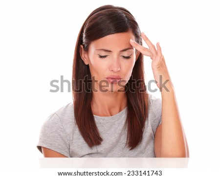 Young female touching her forehead suffering a big headache in white background