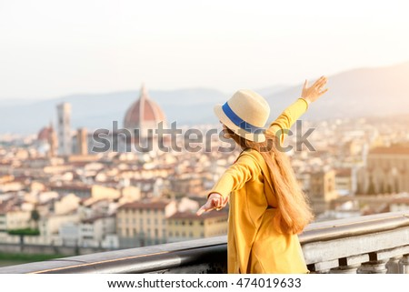 Young female tourist enjoying the view on the old town of Florence from Michelangelo square in the morning in Italy.
