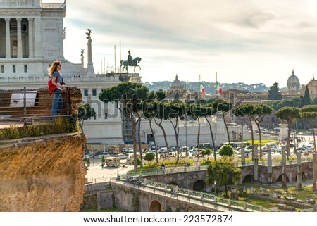 Young female tourist looks at the Forum of Trajan and the Piazza Venezia in Rome, Italy - stock photo