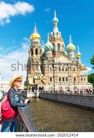 Young female tourist on the background of Church of the Savior on Spilled Blood in Saint Petersburg, Russia - stock photo