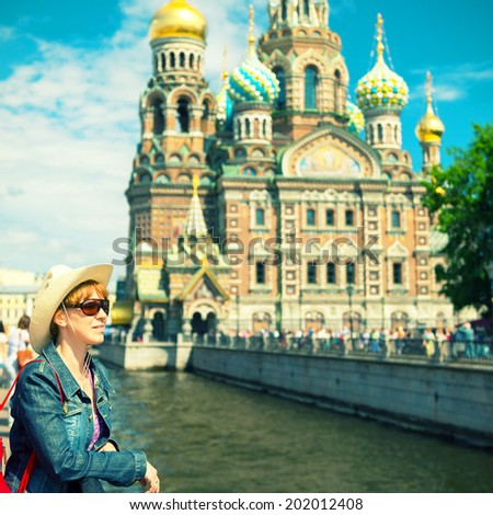 Young female tourist on the background of the Church of the Savior on Spilled Blood (Cathedral of the Resurrection of Christ) in Saint Petersburg, Russia - stock photo