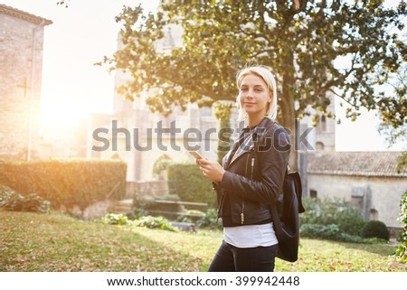 Young female tourist with backpack is using mobile phone for navigation during walking tour in old city. Stylish hipster girl is posing with cell telephone in hands, while is standing outdoors in day - stock photo