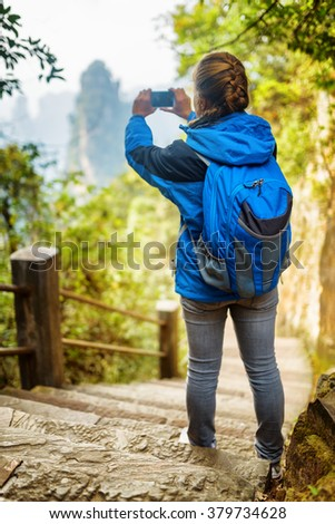 Young female tourist with blue backpack standing on stone stairs among green foliage and taking photo of beautiful mountain view, the Zhangjiajie National Forest Park, Hunan Province, China.
